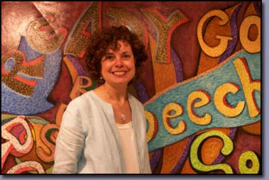 Linda Shears, Interior Designer, Author pictured in front of the Words at Play Mural painted as a volunteer with the Image and Arts Council of Troy, Michigan